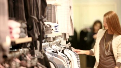stock-footage-attractive-blond-girl-choosing-a-striped-pullover-in-the-mall